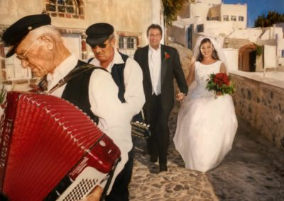 Bride and groom walking down a Mediterranean street with musicians leading the way