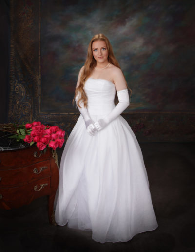 Young woman wearing a white wedding gown and diamond tiara