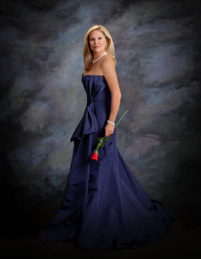 Young woman wearing a purple evening gown holding a red rose posing for picture
