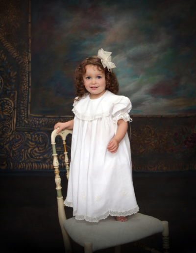 Little girl with curly hair wearing a white dress standing on a chair posing for pictures