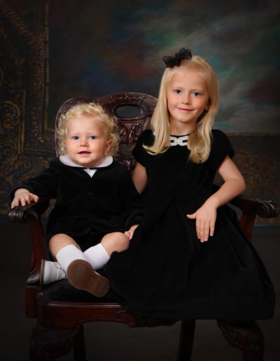 Little boy and girl sitting in a chair wearing black posing for pictures