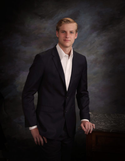 Young man wearing a sport coat resting on an old piece of furniture posing for picture