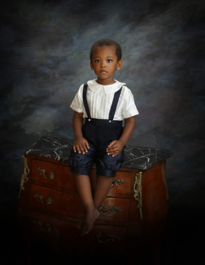 Little boy sitting on a antique chest of drawers with dark background