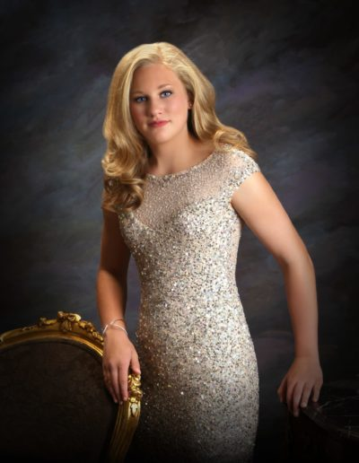Young blonde woman wearing a sparkly dress standing in front of a dark purple painted background