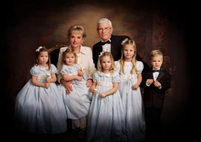 Portrait of dressed up grandparents with their grandchildren standing in front of them