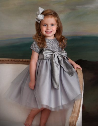 Painting portrait of a little girl wearing a grey satin dress standing on formal couch