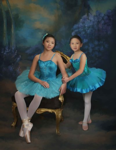 Two girl ballerinas wearing blue sitting in a chair with a painted background of flowers