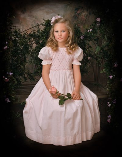 Young blonde girl sitting on a bench wearing a light pink dress trimmed with flowers and holding a pink rose