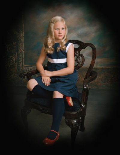 Blonde girl sitting in a velvet and wood chair wearing a dark blue dress with white accents