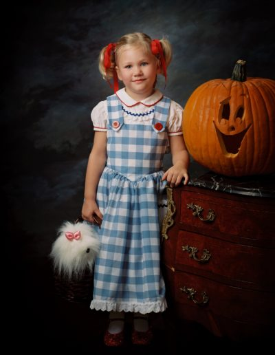 Portrait of a little girl with pigtails and wearing a white and blue checkered dress standing next to a Halloween carved pumpkin