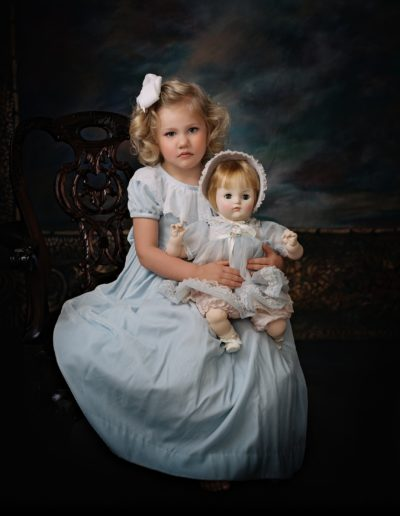Little girl wearing a blue dress holding an old doll with matching dress