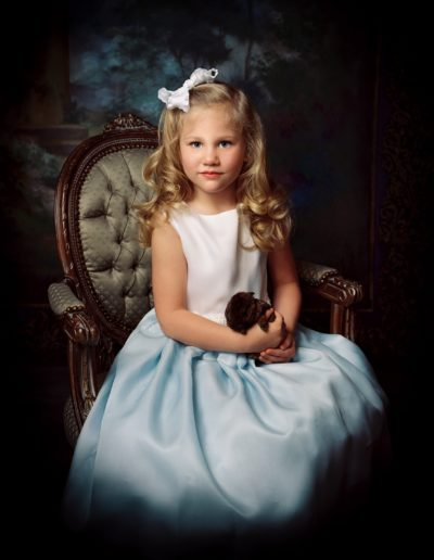 Young girl sitting on an old chair wearing a white and blue hombre dress holding a small brown bunny