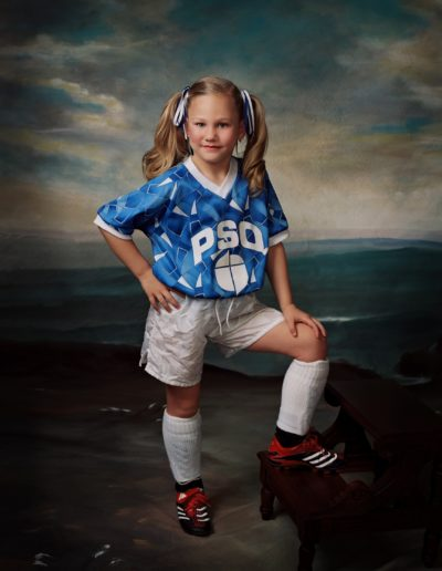 Little girl with pigtails wearing a soccer uniform standing in front of a painted background