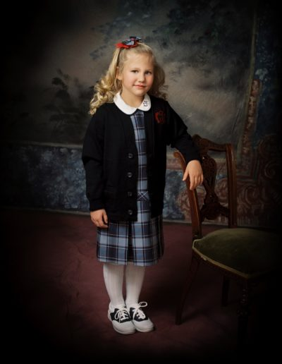 Little girl in Catholic school uniform standing in front of painted background