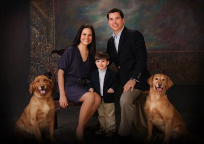Young family dressed up posing with two Golden Retriever dogs and a mural in the background