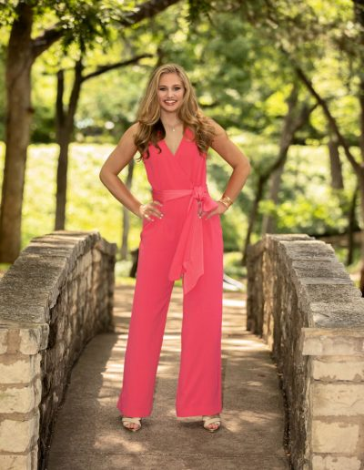 Young blonde woman wearing a pink one-piece pants outfit standing on stone bridge with hands on hips and smiling