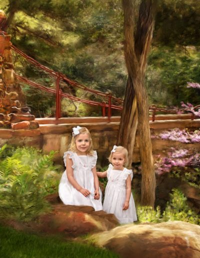Two little blonde girls standing near a painted bridge background