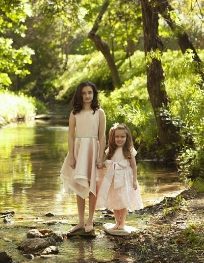 Charis Studios portrait of two girls standing on stones in a creek wearing pink dresses