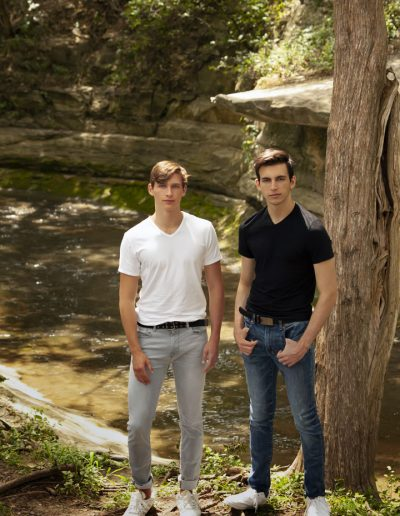 Charis Studios portrait of two young men standing next to a tree with a creek in the background