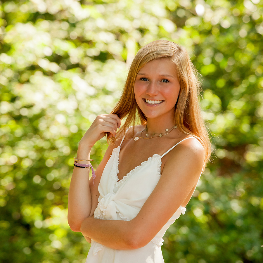 Charis Studios nature picture of blonde girl wearing white dress smiling with trees in background