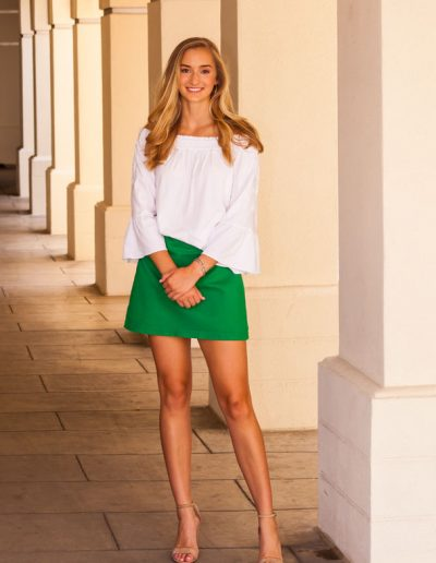 Portrait of blonde young woman wearing a white blouse and green skirt smiling